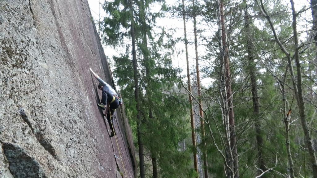 """Aleksi climbing a thin crack line of """"Kolokelmi""""."""